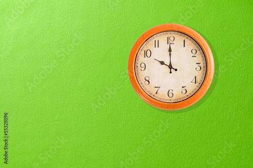 Leinwanddruck Bild Clock showing 10 o'clock on a green wall