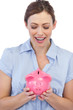 Astonished businesswoman posing with piggy bank