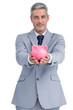 Confident businessman holding piggy bank in both hands