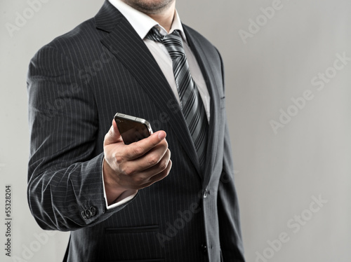 Businessman with cell phone over grey background