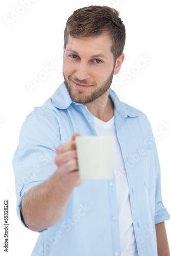 Smiling young model offering a mug