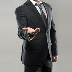 Businessman or director in luxury suit giving something