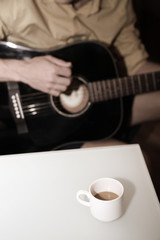 man with guitar and cup of coffee