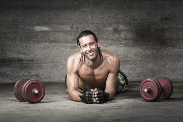 portrait of muscle and smiling athlete lying on the floor