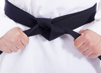 Closeup of a martial arts man tying his black belt