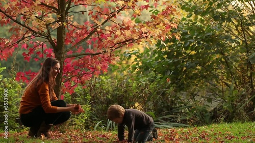 Mum and son throwing colourful autumn leaves