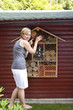 Junge frau zeigt Insektenhotel