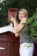 Junge hübsche Frau kontrolliert Vogelhaus