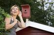Junge Frau hört an Vogelhäuschen