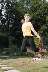 Junge Frau im Garten springt Seil