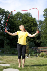 Junge aktive Frau hat Spaß mit Seilspringen