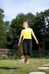Junge Frau springt im Garten Seil