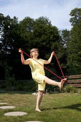 Aktive ältere Frau trainiert im Garten mit dem Seil