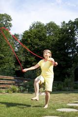 Aktive ältere Frau springt im Garten Seil