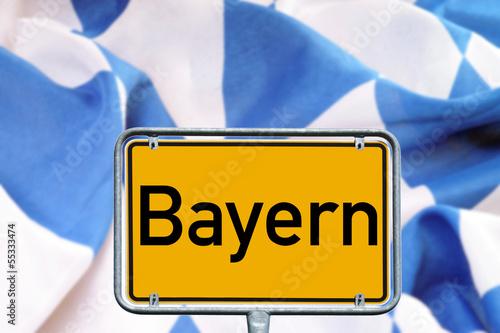 Ortsschild Bayern mit bayerischer Flagge