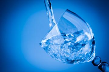Water splashing in a blue glass