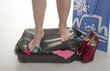 Female holidaymaker standing on broken suitcase