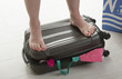 Female holidaymaker standing on suitcase