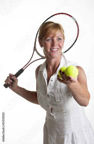 Female tennis player holding racquet and two balls