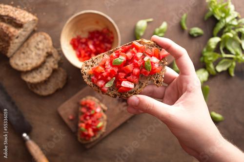 Hand holding Italian bruschetta
