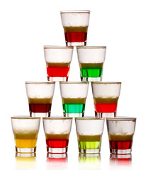 Pyramid of short colored alcohol cocktails isolated on white