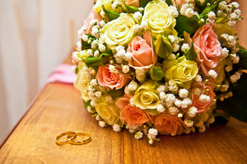 gold rings next to a wedding bouquet