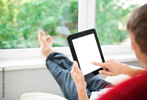 Man using tablet on sofa at home