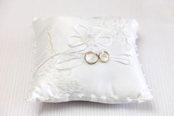 Obrączki ślubne na białej ozdobnej poduszce.