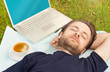 Man sleeping outdoor next to laptop computer and coffee