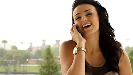 Pretty young woman on mobile outdoors laughing