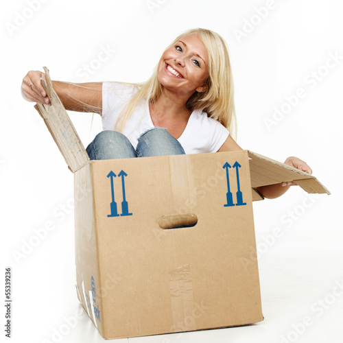 Pretty young woman stting in her moving box