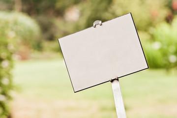 Ein leeres weisses Schild an einem Stiel