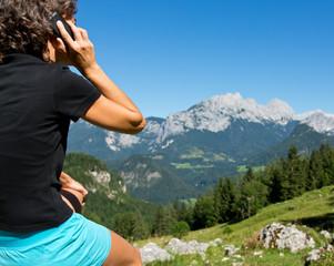 Frau telefoniert aus dem Berg Urlaub nachhause