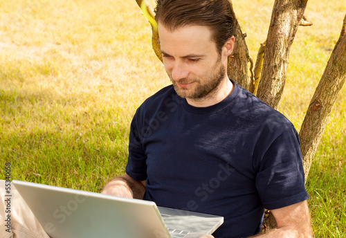 Man working on laptop computer outdoor in a park