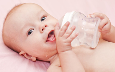 happy baby holding bottle and drinking water