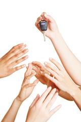 Viele Hände greifen nach Autoschlüssel