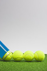 Tennis concepts: four tennis balls close to a container lie on g