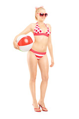 Attractive female in bikini holding a beach ball