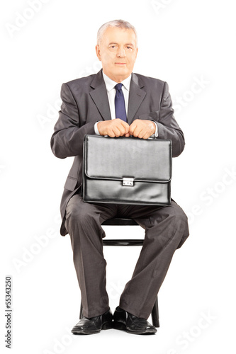 Mature businessman in suit holding a briefcase and waiting