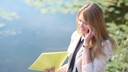 business woman or student on a river bank