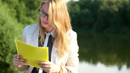 Beautiful business woman or student on a river bank