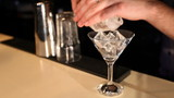 Bartender puts ice cubes in cocktail glass