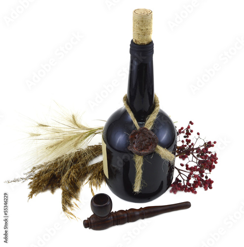 Glass bottle with pipe and berries