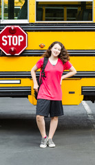 Young Girl Student Standing next to side of Bus