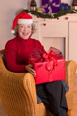 Lachende Seniorin mit Nikolaus-Mütze und Geschenk