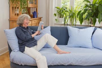 Glückliche Seniorin sitzt  mit tablet-pc auf Sofa