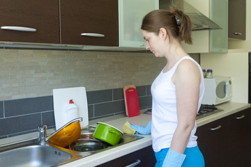 Young girl looking at dishes in the sink