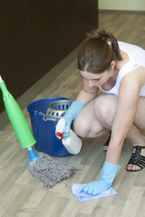 Young girl removing spot from the wooden floor