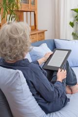 Frau mit grauen Haaren sitzt mit e-Book auf Sofa