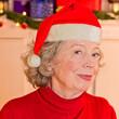 Leinwanddruck Bild - Attraktive Großmutter mit Weihnachtsmann-Mütze